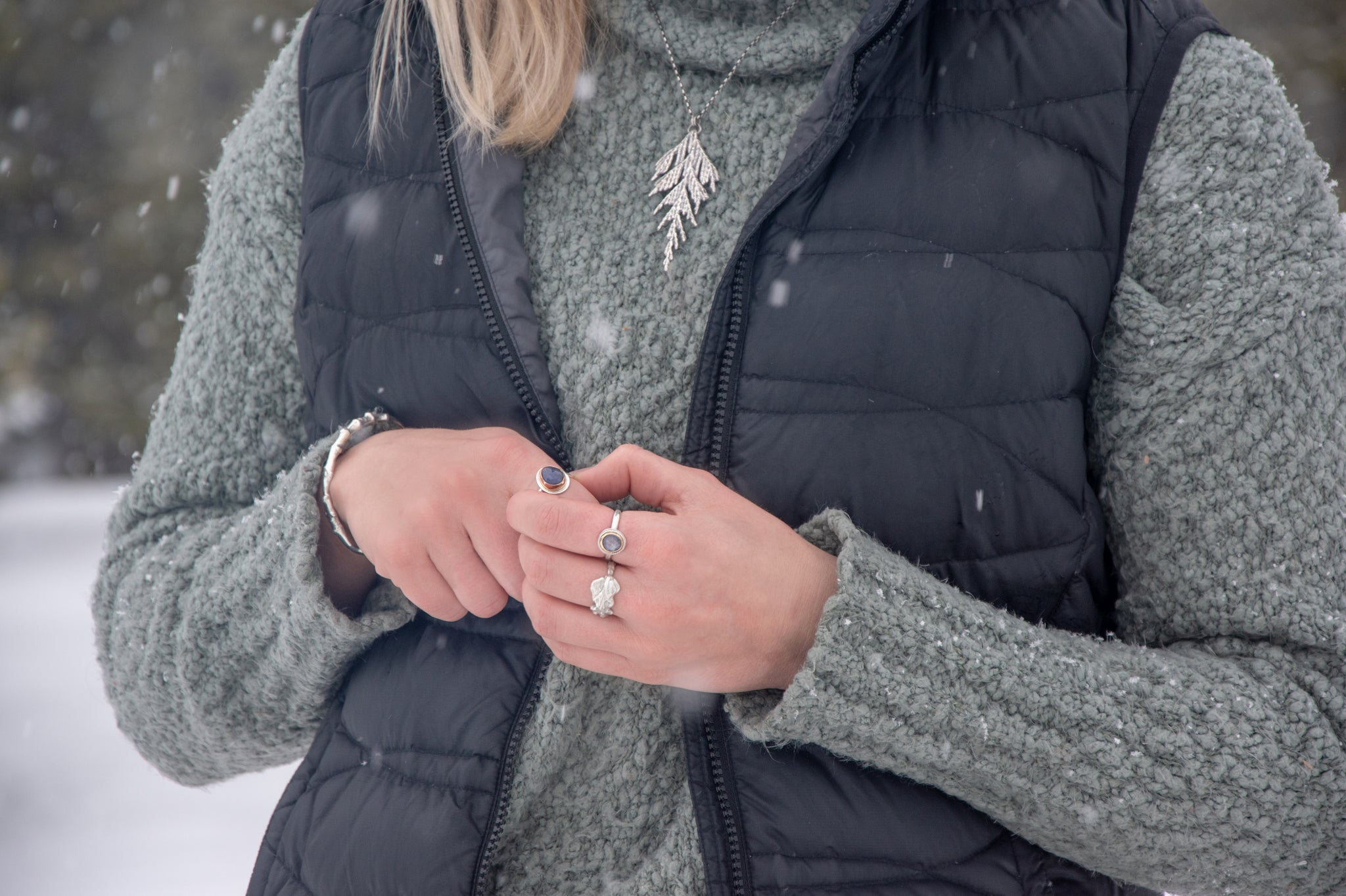 Woman wearing handmade, silver, nature inspired jewelry in winter