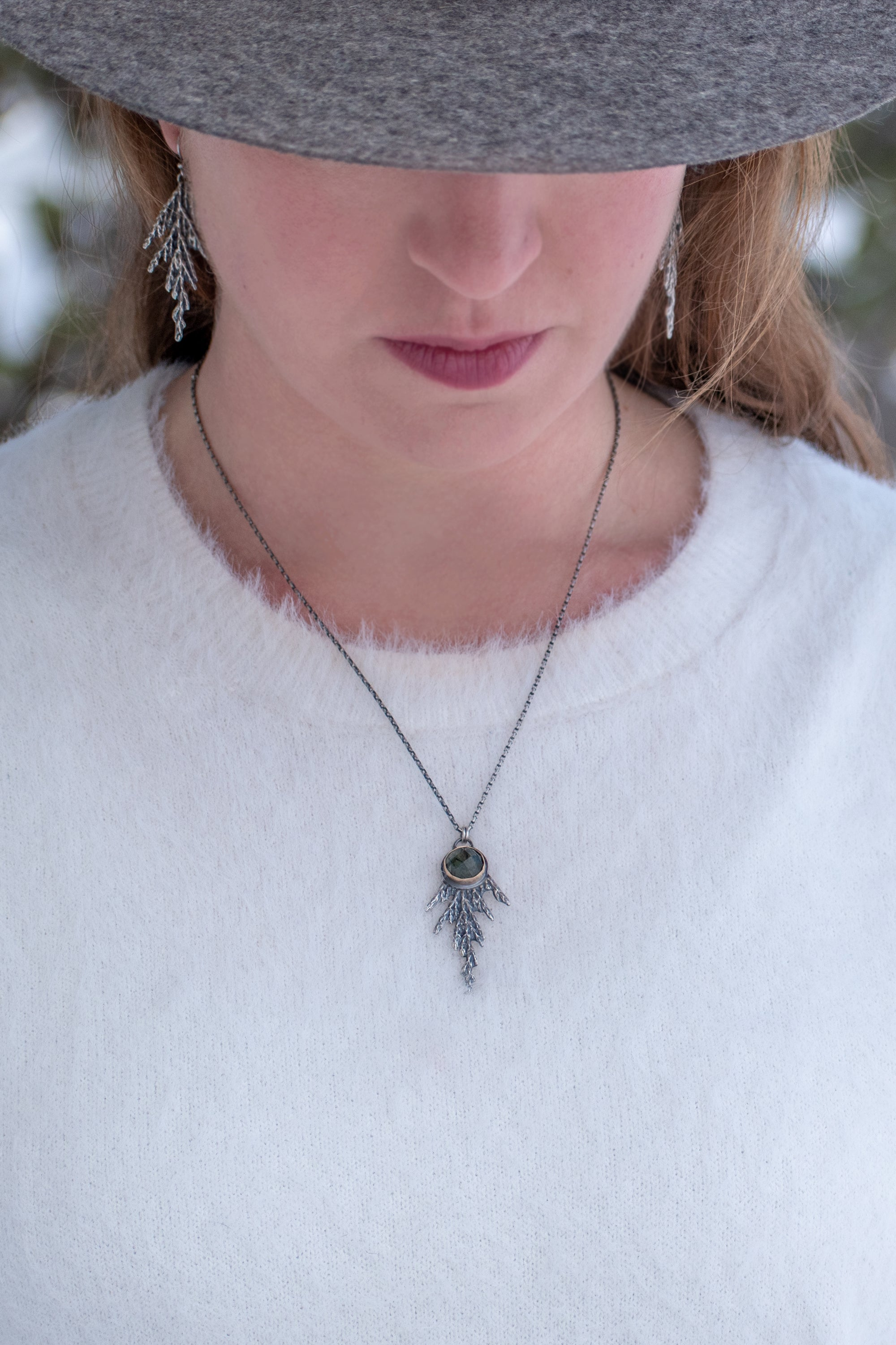 Woman wearing handmade sterling silver cedar necklace with green rutile stone set in 14k gold