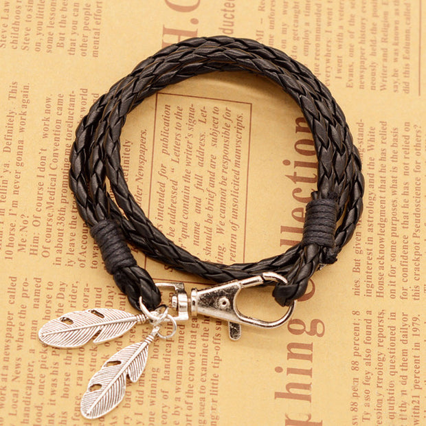 Black braided bracelet with dangling silver feathers
