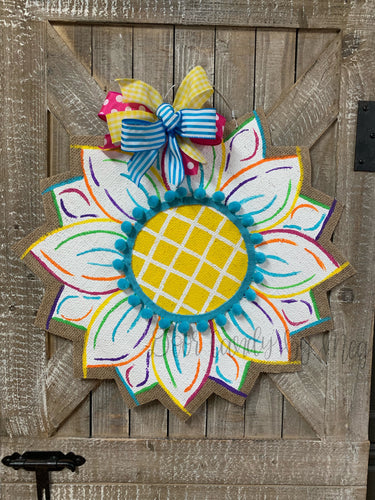 white sunflower door hanger with yellow center, turquoise ball trim and multi color bow