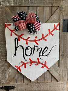 baseball home plate door hanger with hand-lettered home and black and red bow