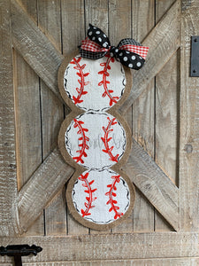 three stacked baseball door hangers with red and black bow