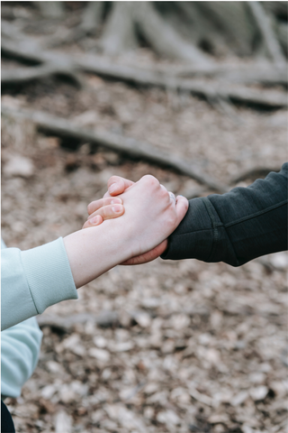 An image of two people holding hands as a sign of support for World Suicide Prevention day