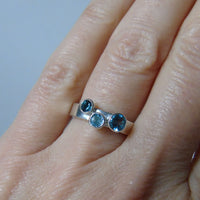 silver ring with three blue topaz