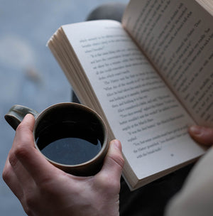 A coffee subscription customer enjoying a cup of freshly brewed Lost Horizon Coffee whilst reading a book