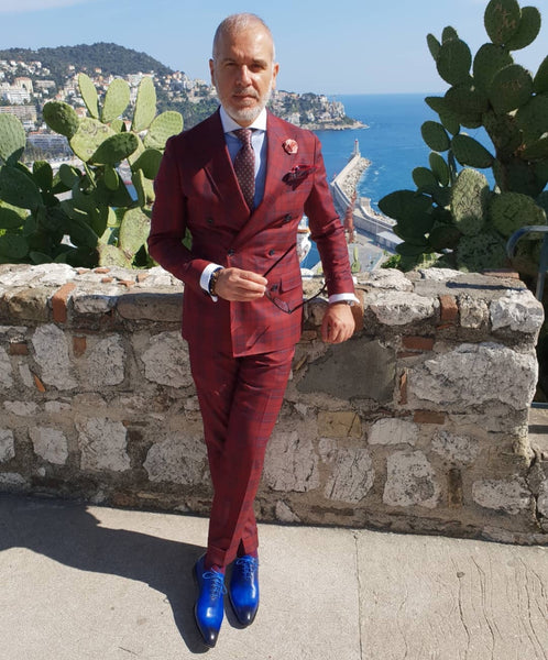 Suited Traveller wearing Thomas Bird custom blue wholecuts with a red prince of Wales suit