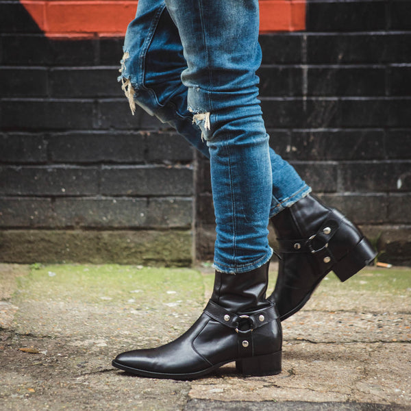 Black leather harness boots with blue jeans