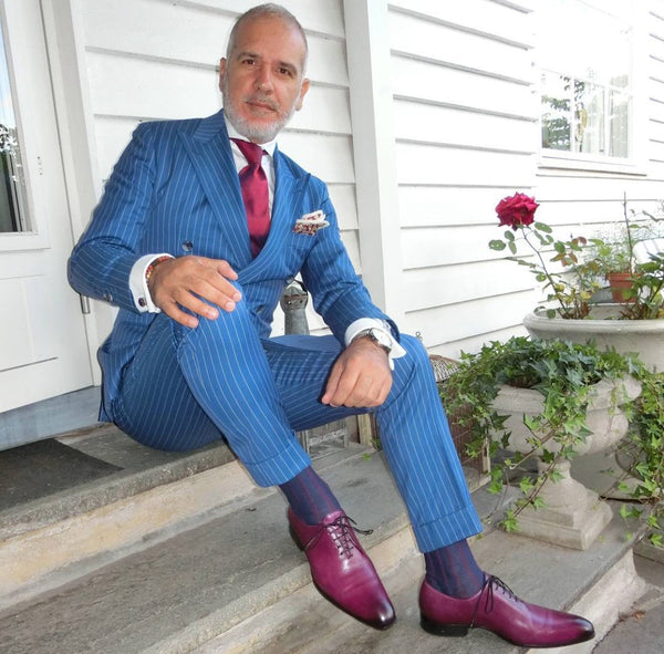 Suited Traveller wearing Thomas Bird plum wholecuts with a blue pin-striped suit