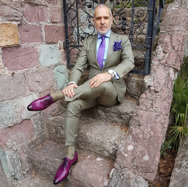 Suited Traveller wearing Thomas Bird plum wholecuts with a pale green suit
