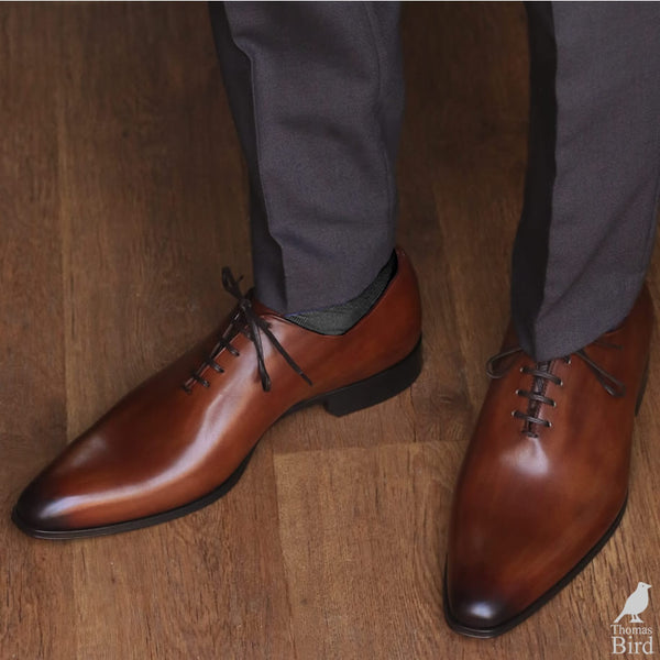 Tan wholecut shoes with grey trousers