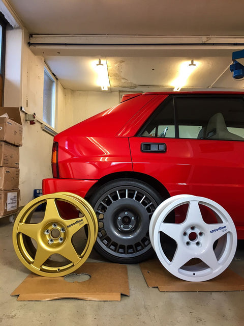 Lancia Delta HF integrale Rosso Monza with OZ style Aero wheels sitting behind two Speedline Corse 5 spoke Race/Rallye wheels