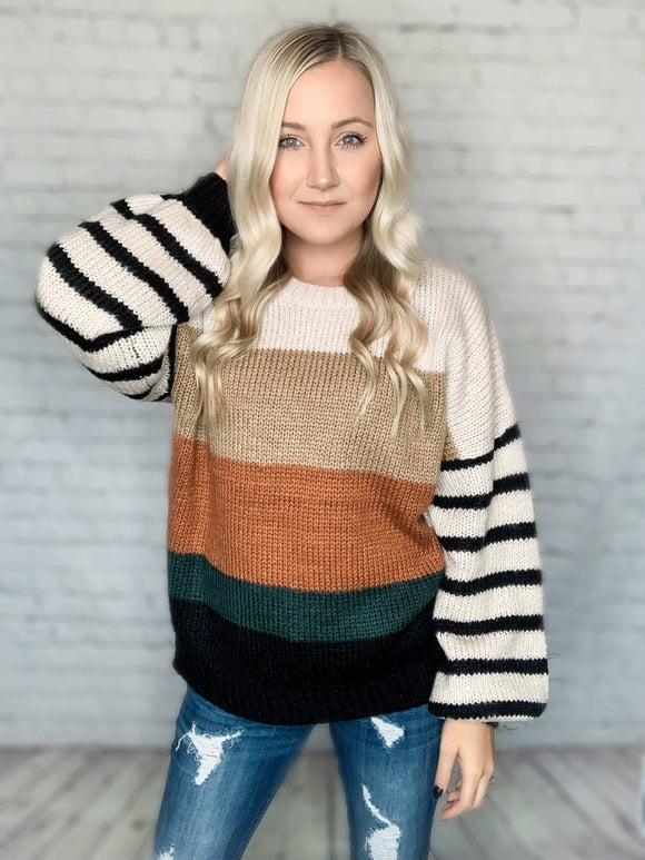 What's not to love about this balloon sleeve colorblock sweater?! This knit sweater features puff sleeves, a round hem neckline, stripes down the sleeves and colorblock pattern on the front and back. It has an oversized and relaxed fit which is perfect when you're wanting to look cute but stay cozy! Pair it with our Kan Can jeans or distressed jeggings for the cutest fall look.  Colorblock Stripe Knit Sweater Black, Camel, Green, Rust & Cream Relaxed Fit Balloon Sleeves