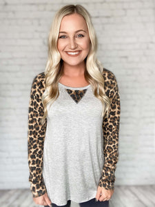 A basic top with a twist! This grey knit raglan gives the perfect chic look with the leopard print details. This top features leopard print sleeves and a roomy body. Comfort & cuteness all in one top! Pair it with our distressed moto jeggings or a pair of our Kan Can jeans! Top the look off with sneakers or booties.  Grey Leopard Print Accents Knit Raglan True to Size 96% Rayon, 4% Spandex Made in the USA