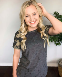 Hiding Out Distressed Camo Tee. This distressed knit top is going to be your new favorite tee with it's super soft fabric. It features camouflage terry raglan sleeves and distressing throughout it's charcoal body.