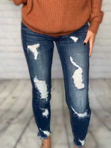 "Our premium denim jeans are going to be your new favorite this fall! They're distressed in all the right places, have a dark wash that pairs great with any top and frayed ankles. The distressing around the ankles in the front & back makes them perfect for booties! These jeans are so easy to dress up or down. Talk about versatile!  Mid Rise Kan Can Jeans Front Distressing Dark Wash Raw Frayed Ankles True to Size 98% Cotton, 2% Spandex 8.5"" Front Rise, 27"" Inseam"