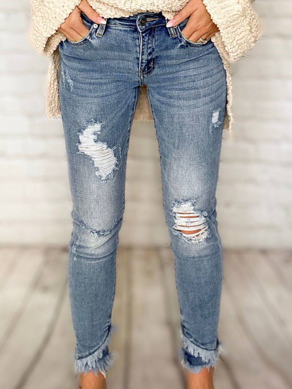 You'll be sure to fall in love with our premium denim jeans! Our Kan Can jeans will hug you in all the right places to accentuate your figure. These skinny jeans feature distressing throughout, a mid rise and tiered frayed ankles. Pair these distressed jeans with your favorite pair of booties for a stylish look this winter.  Mid Rise Kan Can Jeans Distressed Skinny Jeans Soft & Stretchy Medium Light Wash Tiered Frayed Ankles with Slits True to Size 98% Cotton, 2% Spandex 8.5