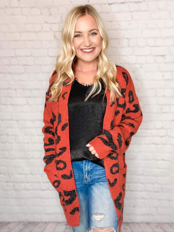 This leopard print cardigan is gorgeous! The bright color and pattern just give you that perfect pop of color! This long duster cardigan features an open front, side pockets and a heavy weighted fit. Pair it with our black lace cami and Kan Cans for the perfect look!  Loose Boxy Fit Open Front Side Pockets 100% Polyester
