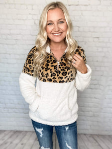 This leopard print sherpa pullover is oh so cozy! The fuzzy material is on the inside and outside of the entire top. This sherpa features leopard print at the top, white throughout the arms and lower body and has a 3/4 zip collar. Wear your normal size for a feminine fit or size up for an oversized fit.  Leopard Print Sherpa Sherpa Material Inside & Out Fold Down Collar 3/4 Zip Collar Middle Pocket True to Size (Size up for Oversized Fit) 65% Polyester, 35% Cotton