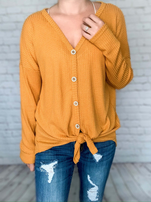 This waffle knit thermal is going to be your new favorite fall basic. This long sleeve button up top is lightweight and oh so comfy. The mustard color and front tie knot give it such a chic look for fall. You can even wear this top off the shoulder with a bralette!   Mustard Color Thermal Waffle Knit Long Sleeves Self Tying Front Knot Button-Up Stretchy Material True to Size 89% Polyester, 8% Rayon, 3% Spandex
