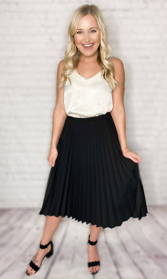 This skirt is such a chic way to dress up an outfit! You can pair this pleated black skirt with our satin lace cami tank and a pair of heels for a dressier look or pair it with one of our graphic tees and a pair of sneakers for an edgy vibe. This pleated skirt features an elastic waistband for all day comfort, a timeless black color and can be worn as a midi or maxi skirt depending on your height. This skirt also comes in mauve.  Black Pleated Skirt Elastic Waistband 96% Polyester, 4% Spandex