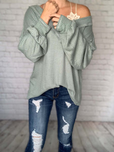 This waffle knit thermal makes for the perfect fall top. This long sleeve top is cozy and roomy - talk about the comfiest shirt! This dusty sage thermal features puff balloon sleeves, a v-neckline, stitching detail and it can even be worn off the shoulder! Pair this waffle knit top with one of our bralettes for a chic fall look!   Dusty Sage Color Thermal Waffle Knit V-neck Stitching Detail Oversized Fit True to Size 100% Rayon Made in the USA