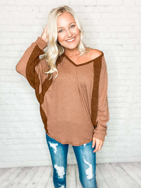 Our Sahara Dolman Sleeve top features the perfect fall hues with creamy tans and a touch of contrast. Designed with a v-neckline, round hem, dolman sleeves and a loose fit for comfort. Throw on a wide brimmed hat, booties and jeans with this top for a chic fall look!   Brown Waffle Knit Dolman/Batwing Long Sleeves V-neckline Round Hem Loose Fit 80% Polyester, 15% Rayon, 5% Spandex Made in the USA