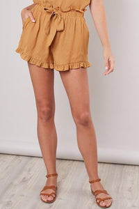Sun Kissed Woven Flounce Shorts in Inka Gold provide a flowy fit with an elastic waistband and self typing bow. Flounce/ruffle details at the bottom hem. These paperbag shorts are high waisted and true to size.