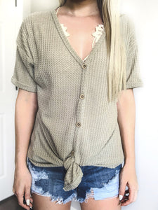 These waffle knits are going to be your new favorite summer basic. They're lightweight and oh so comfy. The rolled sleeves and front tie knot give it such a chic look. You can even wear this top off the shoulder with a bralette!   Sage Thermal Waffle Knit Short Sleeve Self Tying Front Knot Functioning Buttons Rolled Sleeves Stretchy Material True to Size 87% Polyester, 10% Rayon, 3% Spandex Brooke is 5'4 and is wearing a size small. Styled with our bralettes. This top is also available in blush.
