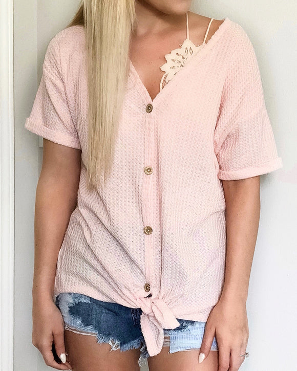 These waffle knits are going to be your new favorite summer basic. They're lightweight and oh so comfy. The rolled sleeves and front tie knot give it such a chic look. You can even wear this top off the shoulder with a bralette!   Blush Thermal Waffle Knit Short Sleeve Self Tying Front Knot Button-Up Rolled Sleeves Stretchy Material True to Size 87% Polyester, 10% Rayon, 3% Spandex 9.5