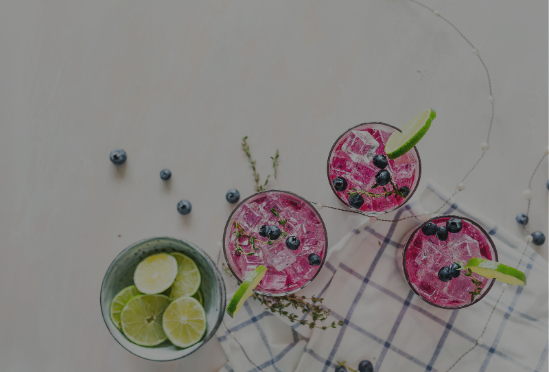 Pink refreshing summer drinks with blueberries and limes on a marble kitchen counter