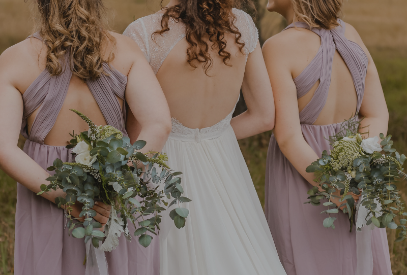 Summer wedding photoshoot inspiration includes bride and bridesmaids holding bouquets from behind