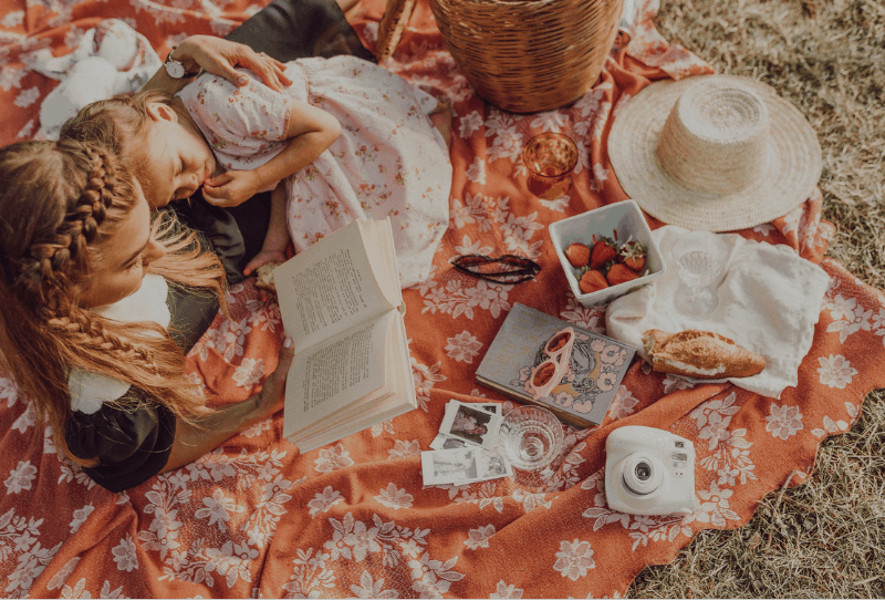 Cute mommy blogger and three year old daughter having a picnic in the park with a book, food and picnic basket