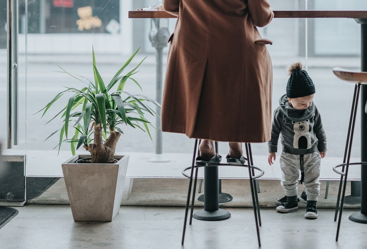 Stylish working mom and fashion blogger sitting in a cafe with her toddler son