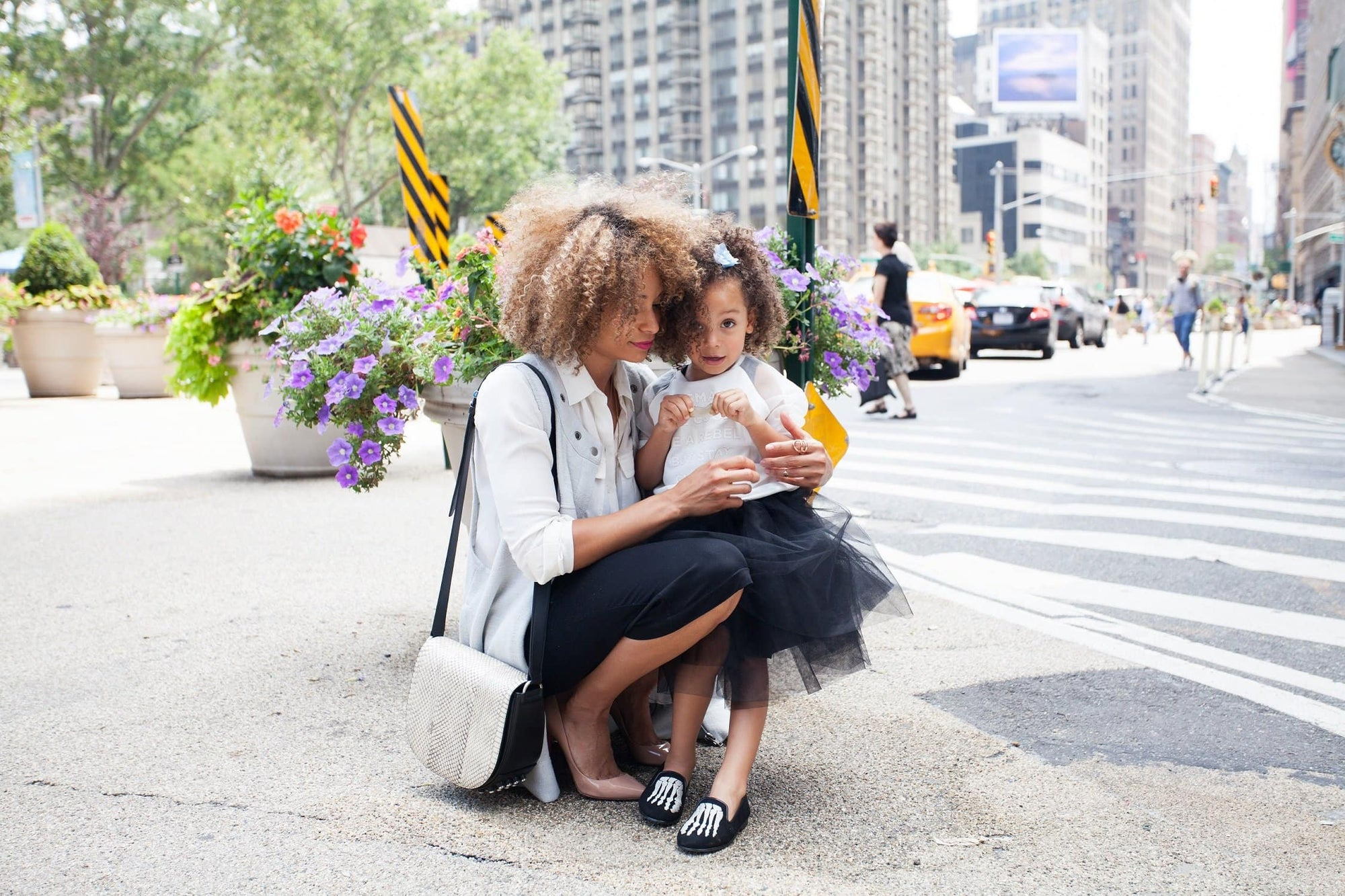 Trendy young girl hugging stylish working mom in New York City