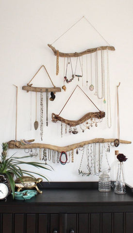 Driftwood jewelry organizer hanging on white wall with gold and sterling silver necklaces