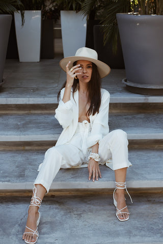 Miami fashion blogger Iron N Salt Daniela Moreno sitting on steps posing in white blazer and pants