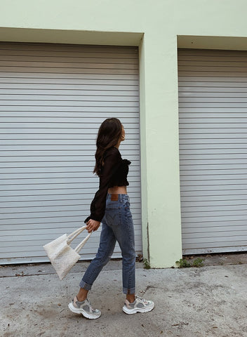 Daniela Moreno walking down the street in jeans and crop top with pearl bag