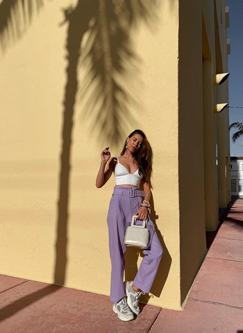 Miami Fashion blogger Daniela Moreno leaning on wall in purple pants and sneakers with pearl bag