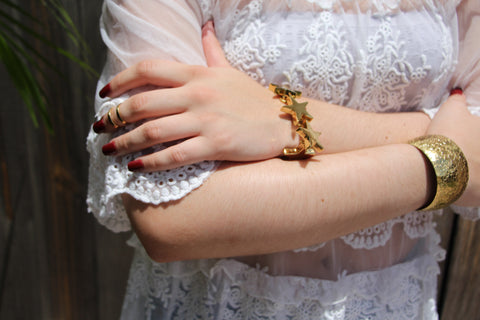 Girl crossing her arms with gold star bracelet and cuff
