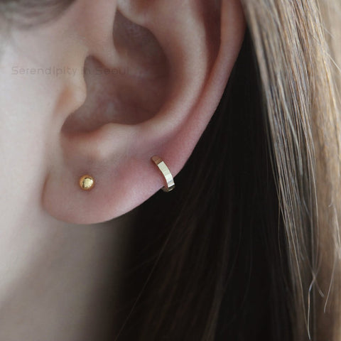 Girl ear with gold stud and hoop earring