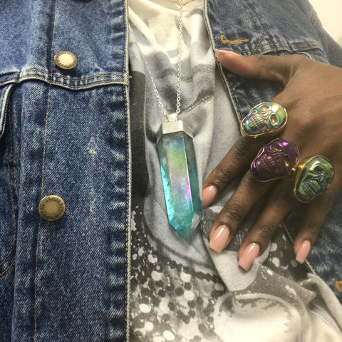 Fashion blogger wearing quartz pendant with skull rings in denim jacket