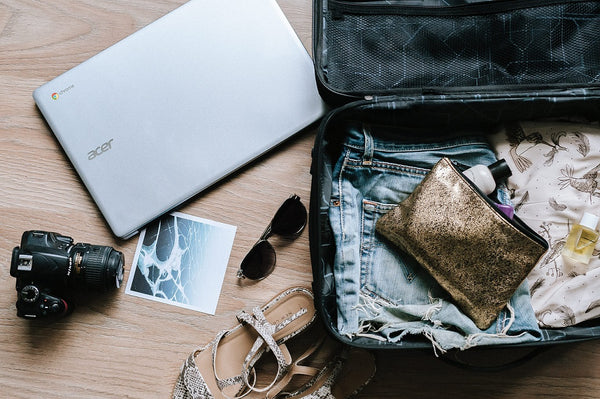 Flatlay shot of blogger packing the essentials to take on summer vacation