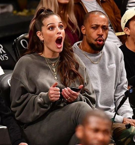 Ashley Graham sitting court side at a basketball game in grey sweater and jeans
