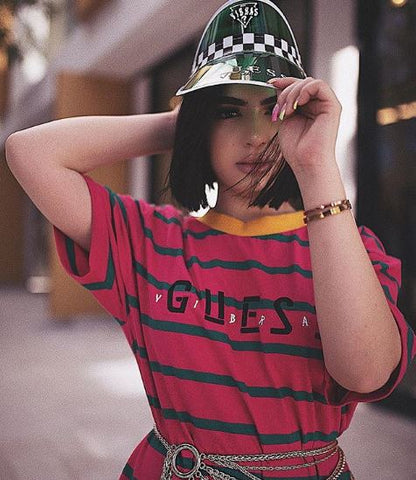 Fashion blogger posing in over sized Guess red and black striped t-shirt with silver belt and visor