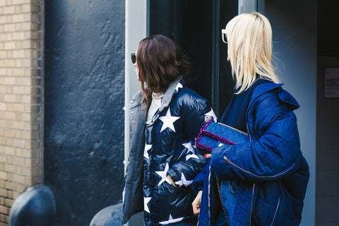 Two fashion bloggers in puffer jackets looking away while being photographed in New York City