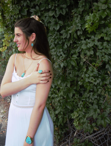 Girl in sleeping beauty turquoise jewelry in white dress posing outside