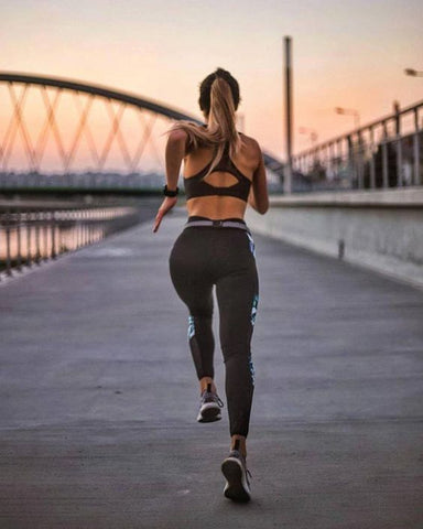 A woman running away from the camera at sunset