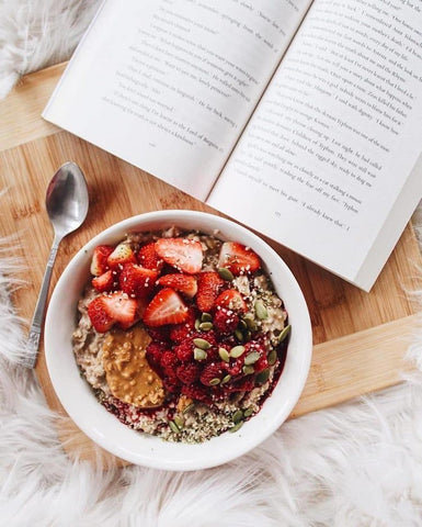 Acai bowl on a wooden board next to an open book
