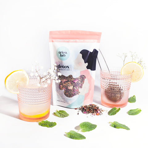 Trico.Lab Detox Organic Tea pouch with two glasses filled with tea and flowers around it