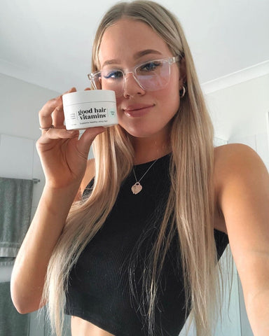 Model with long blonde hair holding her Trico.Lab Good Hair Vitamins